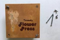 ....und drückt den ganzen Stapel aus Pflanzen und Papieren zusammen.