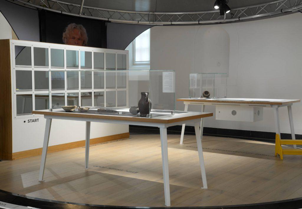 Hinter den Spiegelscheiben des Vitrinenschrankes warten Gegenstände in mittelalterlicher und moderner Variante darauf, zusammengeführt zu werden. Foto: © GDKE RLP, LMMZ, Ursula Rudischer